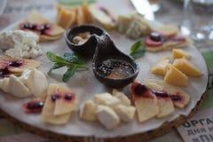 Disco del queso con la rebanada de fruta, de miel y de nuez en el centro en el tablero de madera Tablero de la cena, bocado imagen de archivo libre de regalías