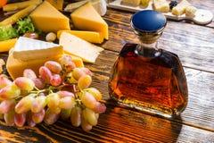 Disco del queso, uvas y una jarra del brandy Foto de archivo