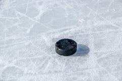 Disco di gomma di hokey nero sulla pista di pattinaggio di ghiaccio Immagini Stock Libere da Diritti