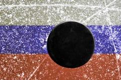 Disco di gomma di hokey nero sulla pista di pattinaggio di ghiaccio Immagine Stock