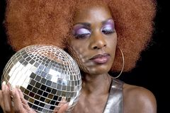 Disco Diva 2 (Eyes Closed). Attractive black model wearing purple eye makeup and holding a disco ball Royalty Free Stock Photography