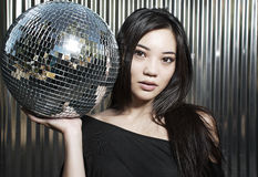 Disco diva Asian beauty model. Beautiful young Asian woman holding disco ball mirror in club Royalty Free Stock Photo