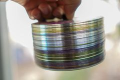 Disco do CD empilhado em uma pá de pedreiro da mão em homens imagens de stock royalty free