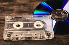 Disco do vinil e cassetes de banda magnética na tabela de madeira Imagem de Stock