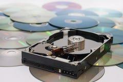 Disco duro abierto viejo en una pila de compact-disc Foto de archivo