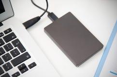 Disco duro externo del disco de reserva conectado con el ordenador portátil Fotografía de archivo
