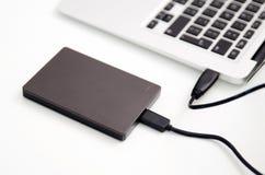 Disco duro externo del disco de reserva conectado con el ordenador portátil Fotos de archivo libres de regalías