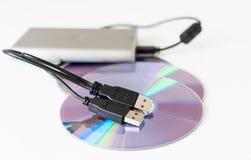Disco duro externo y discos cd Fotos de archivo