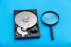 Disco duro y lupa del ordenador fotografía de archivo