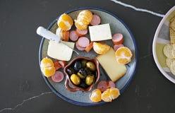 Disco estacional del aperitivo con las aceitunas, el queso, la carne y las naranjas imágenes de archivo libres de regalías