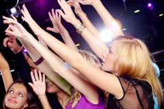 Disco fun. Photo of smiling friends raising arms during the party in excitement royalty free stock photos