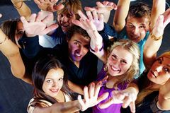 Disco fun. Photo of smiling friends raising arms during the party in excitement royalty free stock image