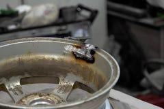 Disco fuso automobilistico durante la riparazione saldando al punto spaccato dopo la caduta in un foro sulla strada in un'officin fotografia stock libera da diritti