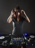 Disco-jóquei fêmea em sua plataforma com fones de ouvido Imagens de Stock Royalty Free