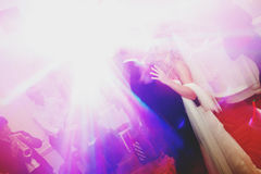 Disco lights shine over a dancing wedding couple royalty free stock photography