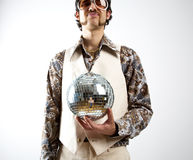 Disco Man. Portrait of a retro man in a 1970s leisure suit and sunglasses holding a disco ball - mirror ball royalty free stock image