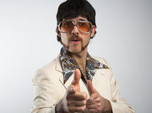 Disco Man. Portrait of a retro man in a 1970s leisure suit and sunglasses pointing to the camera Stock Images