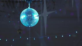 Disco mirror ball. Blue sphere or colorful disco mirror ball reflecting light spots and hanging on the ceiling in the dark of night club or pub. Retro party in stock video footage