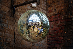 Disco mirror ball in front of an old brick wall on a grungy part Stock Photo