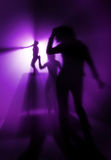 Disco party. Silhouettes of people on discothque in purple light Royalty Free Stock Photos