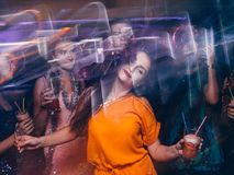 Disco party in night club in blurred motion. Happy friends dancing at Christmas celebration, active New Year company, modern youth life Royalty Free Stock Photo