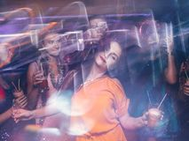Disco party in night club in blurred motion. Happy friends dancing at Christmas celebration, active New Year company, modern youth life Stock Photo