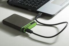 Disco rígido externo verde com cabo no branco Fotografia de Stock