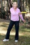 Disco volador que lanza de la mujer mayor en parque Foto de archivo