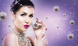 Disco woman wearing silver accessories on purple backgound Stock Photo