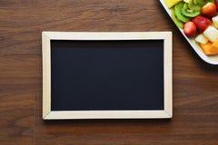 Disco y pizarra de la fruta con el copyspace en una tableta de madera Fotografía de archivo