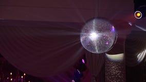 Discobal met heldere stralen, de achtergrond van de nachtpartij discobal het hangen van het plafond glanst bij de partij De Bal v stock footage