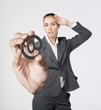 Discomfort businesswoman holding a @ symbol. A studio portrait of a  discomfort businesswoman holding a @ symbol Royalty Free Stock Photography