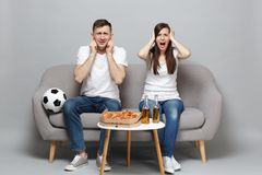 Disconcerted couple woman man football fans cheer up support favorite team covering ears putting hands on head isolated. Disconcerted couple women men football royalty free stock image
