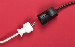 Disconnected white european power cable plug with connector. Disconnected white european power cable plug with black connector cable on red background royalty free stock image