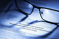 Disconnection Warning Notice. A disconnection notice to pay a bill with reading glasses Royalty Free Stock Photography