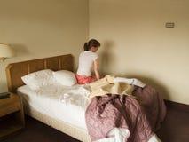 Disconsolate Frau, die auf Hotelbett sitzt Stockbild