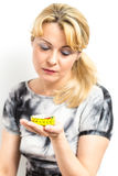 Disconsolate young woman looking at a tape measure Royalty Free Stock Images