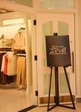 Disconte o anúncio do sinal na entrada da loja de pano Fotos de Stock Royalty Free