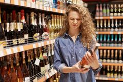 Discontent curly young woman in denim clothes looks with unhappy expression at bottle of wine, reads information abut products, ne. Eds more sugar, dislikes stock images