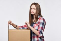Disappointed girl opening a box. Discontent disappointed girl opening a box looking at camera Royalty Free Stock Photo