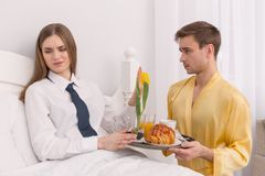 Discontent woman lying in bed. I dislike cookies. Displeased dominant women wearing a tie and her husband bringing her breakfast Stock Image