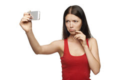 Discontent woman taking pictures of herself through cellphone Stock Photos