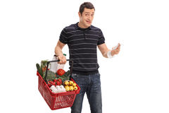 Discontent young man holding a shopping bill Royalty Free Stock Photography