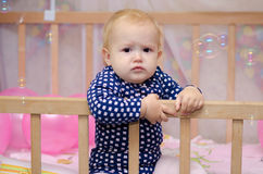 Discontented baby girl. Dissatisfied baby girl sitting in a crib and looking at soap bubbles royalty free stock image