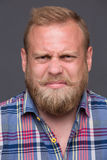 Discontented bearded man. Profile of discontented bearded man on dark grey. Short-haired blond man in plaid shirt frowning disgust because of bad mood royalty free stock photos