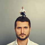 Discontented man with happy man on the head. Portrait of discontented man with happy man on the head stock photography
