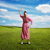 Discontented screaming housewife. Holding rolling pin and looking at camera. photo at outdoor stock photography