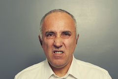Discontented senior man over dark. Background royalty free stock image