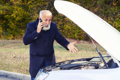 Discontented senior man talking on the phone. And looking under the hood of breakdown car royalty free stock images