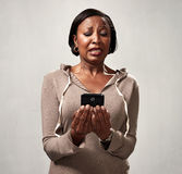Discontented woman with smartphone. Black mature woman with cellphone disgusted face expression royalty free stock photo